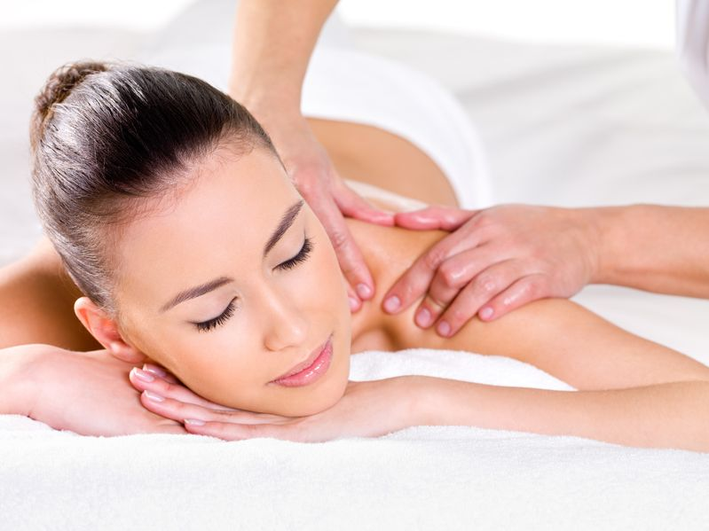 12349868 - young woman having massage on her shoulder in spa salon - horizontal